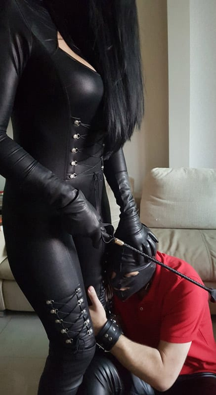Dubai Mistress in a black leather jumpsuit, black leather gloves, is carrying a whip while putting her hand on the latex mask of the submissive who is holding her leg.
