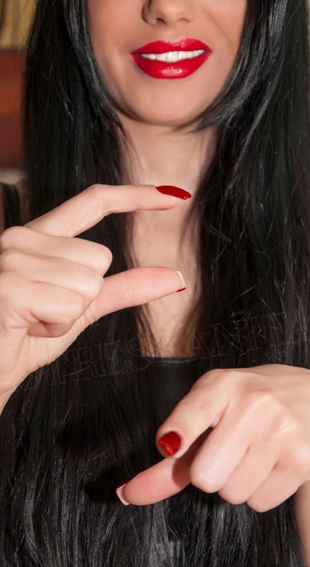 U.A.E. Mistress Anita is laughing and pointing with one hand and showing a gesture of a small size with the other hand indicating small penis humiliation.